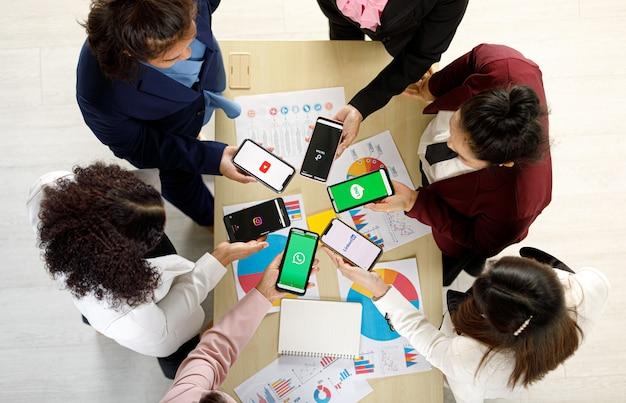 Bangkok/thailand - 06. august 2021: menschen halten smartphones verschiedener marken und betriebssysteme mit verschiedenen logos von sozialen anwendungen, twitter, instagram, tiktok, linkedin, line, youtube.