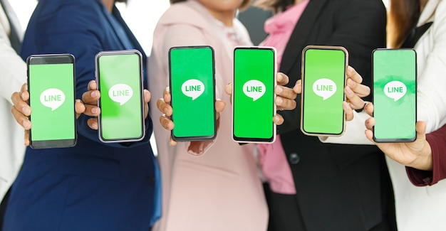 Bangkok/thailand - 06. august 2021: menschen halten smartphones verschiedener marken und verschiedener betriebssysteme mit dem logo von line, den beliebten social-network-anwendungen.
