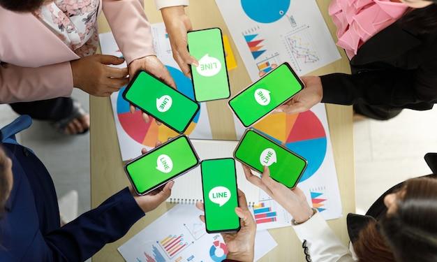 Bangkok/thailand - 06. august 2021: menschen halten smartphones verschiedener marken und verschiedener betriebssysteme mit logos der line-app, einer der beliebtesten messege-anwendungen.
