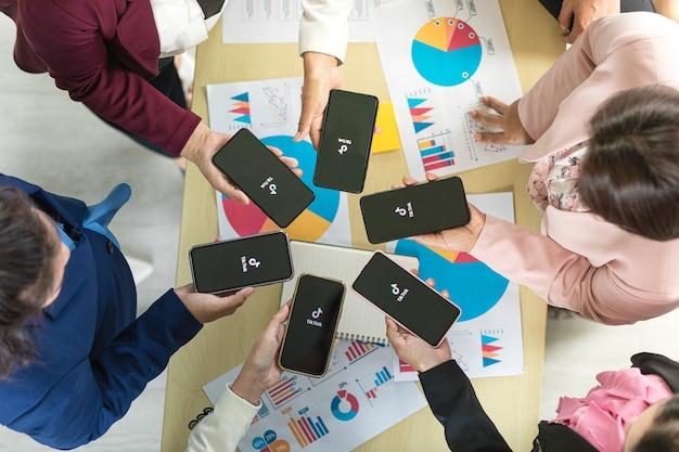 Bangkok/thailand - 06. august 2021: menschen halten smartphones verschiedener marken und verschiedener betriebssysteme mit logos tiktok, eines der beliebtesten sozialen videonetzwerke.
