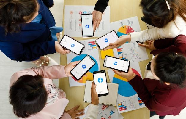 Bangkok/thailand - 06. august 2021: menschen halten smartphones verschiedener marken und verschiedener betriebssysteme mit logos von facebook, den beliebtesten social-network-anwendungen.