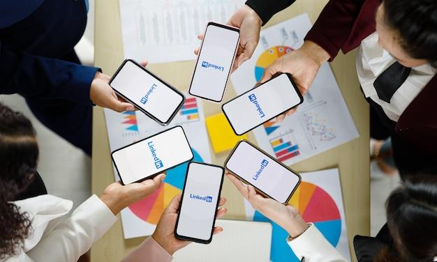 Bangkok/thailand - 06. august 2021: menschen halten smartphones verschiedener marken und verschiedener betriebssysteme mit logos von linkedin, soziale anwendungen.