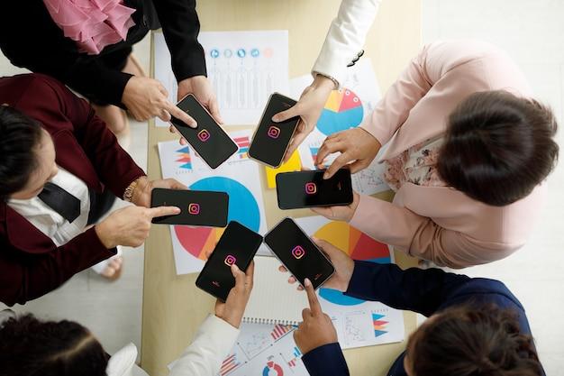Bangkok/thailand - 06. august 2021: menschen halten smartphones verschiedener marken und verschiedener betriebssysteme mit logos von sozialen instagram-anwendungen.