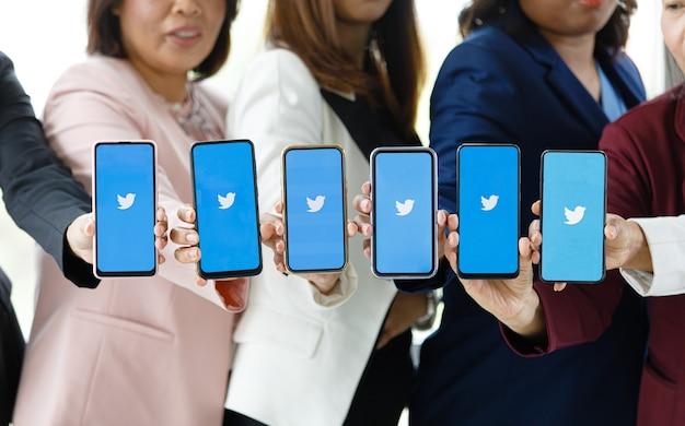Bangkok/thailand - 06. august 2021: menschen halten smartphones verschiedener marken und verschiedener betriebssysteme mit logos von twitter-social-apps.