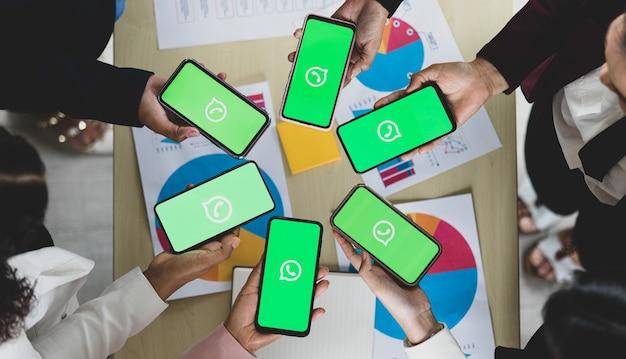 Bangkok/thailand - 06. august 2021: menschen halten smartphones verschiedener marken und verschiedener betriebssysteme mit logos von whatapp, beliebten social-network-messe-anwendungen.