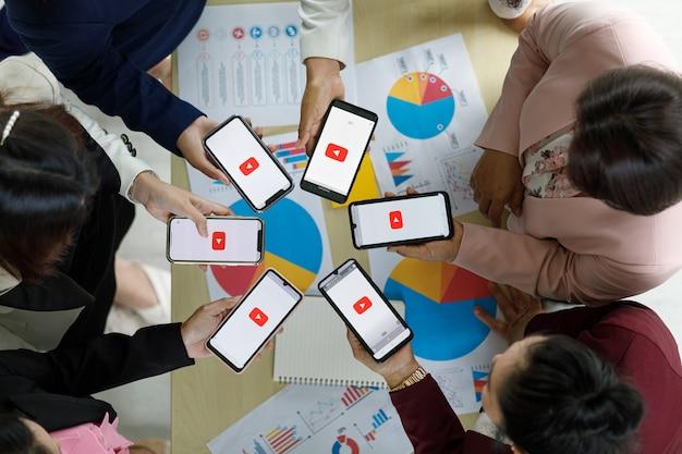 Bangkok/thailand - 06. august 2021: menschen halten smartphones verschiedener marken und verschiedener betriebssysteme mit logos youtube, dem beliebtesten videoportal der welt.