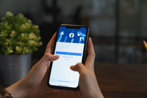 Bangkok, thailand - 30. märz 2020: hand hält telefon und facebook-bildschirm auf apple iphone, social media verwenden für den informationsaustausch und das networking.