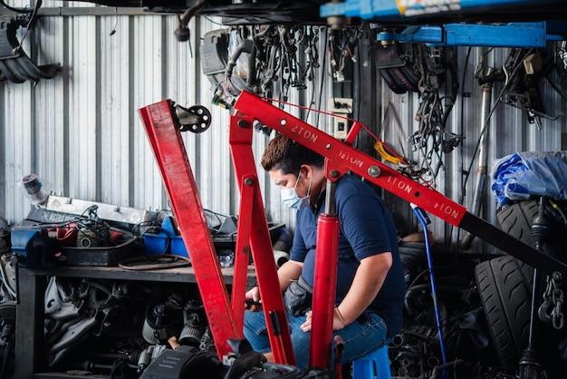 Bangkok, thailand - 4. april 2020: nicht identifizierter automechaniker oder servicemann, der einen automotor auf reparatur- und reparaturprobleme in der autowerkstatt oder in der werkstatt überprüft