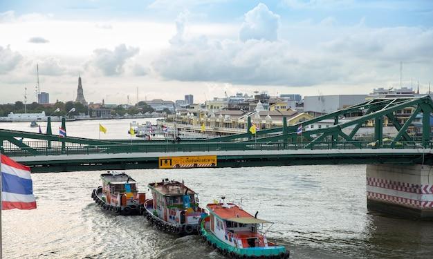 Bangkok/thailand - 7. juli 2020: bootsfrachtschiffe, die unter der brücke vorbeifahren blick vom chao phraya sky park, chao phraya river in der nähe der phra pokklao bridge in thonburi, bangkok, thailand.