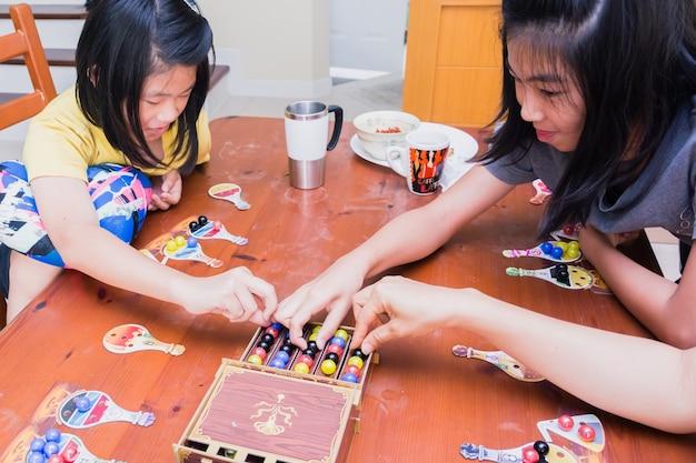 Bangkok thailand, am 18. märz 2018: kinder und eltern, die das brettspiel innen, familienkonzept spielen