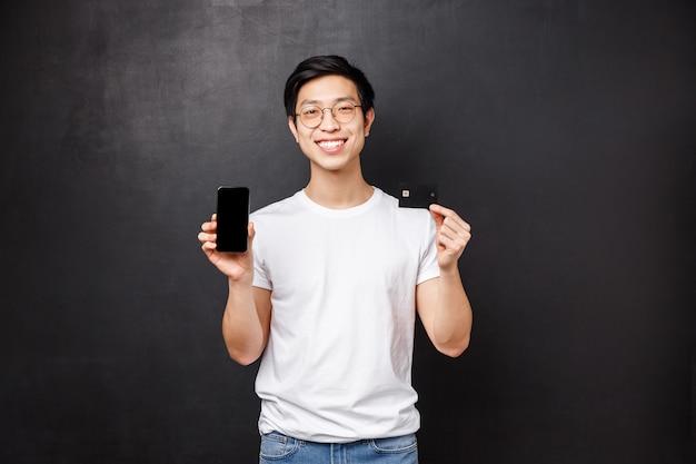 Bank-, finanz- und zahlungskonzept. porträt des einfachen asiatischen kerls im weißen t-shirt, das neue anwendung für bankbenutzer einführt, kreditkarte und handy hält und auf schwarzer wand lächelt