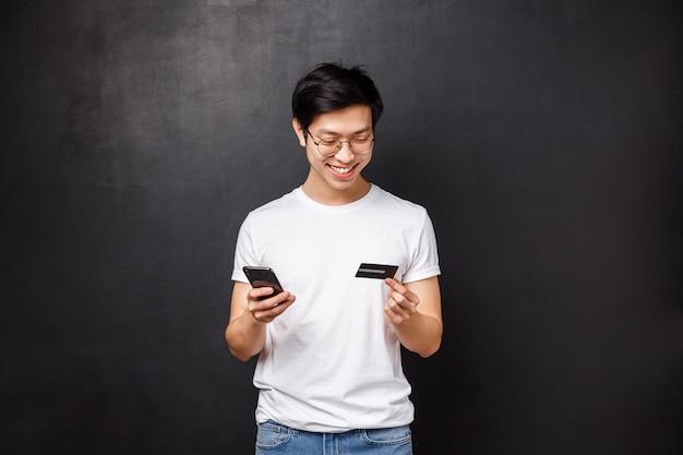Bank-, finanz- und zahlungskonzept. porträt des fröhlichen asiatischen mannes im t-shirt, handy und kreditkarte haltend, rechnungsinformationen einfügen, produkte online kaufen, flugtickets mit app buchen