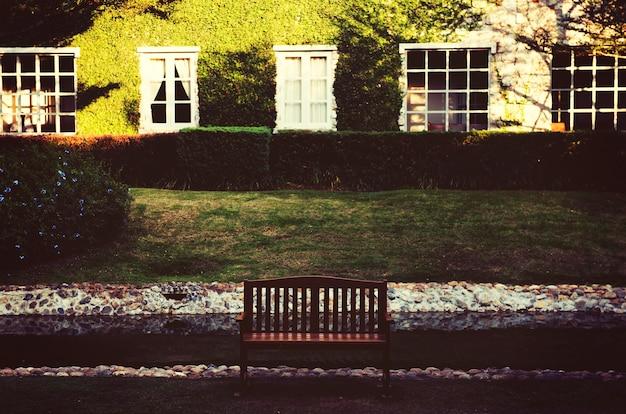 Bank für entspannung vor dem garten des grünen grases