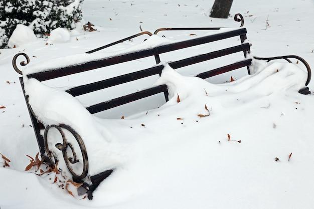 Bank im park mit schneefall