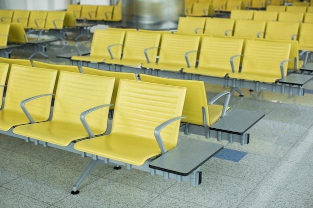 Bank im terminal des flughafens. leerer wartebereich des flughafenterminals mit stühlen.