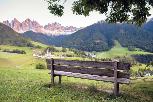 Bank mit bergdorf und bergen auf hintergrund