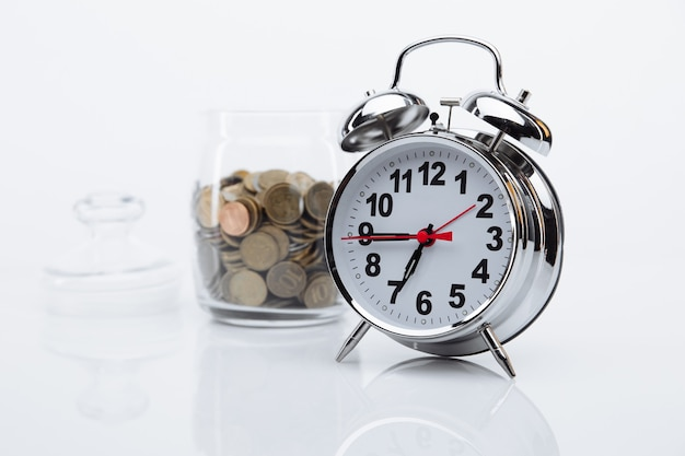 Bank mit münzen und wecker nahaufnahme. zeit ist geldkonzept