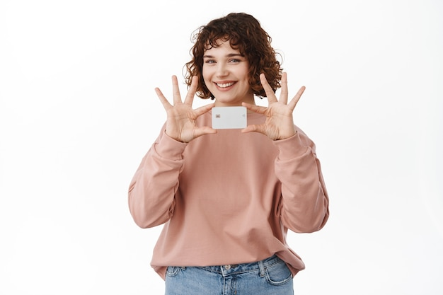 Bank- und finanzkonzept. schönes mädchen hält und zeigt kreditkarte, lächelt glücklich und kündigt neue banking-funktion an