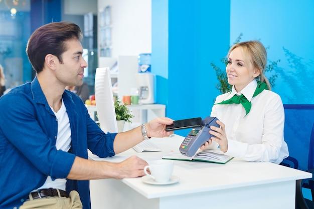 Bankkunde, die mit smartphone im bankbüro zahlt