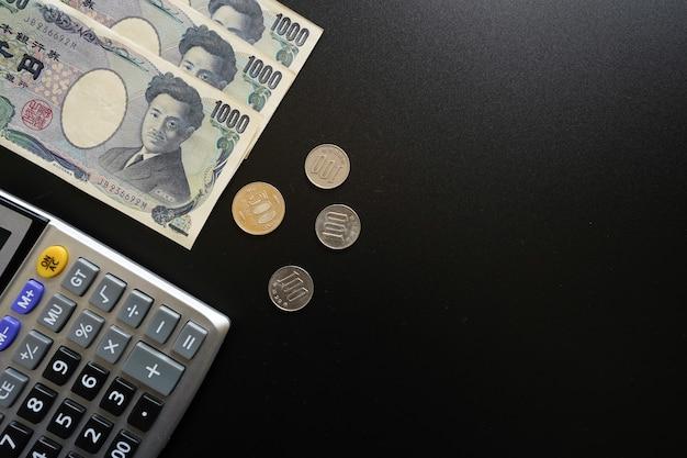 Banknote und münzen der japanischen währung auf dunklem hintergrund.