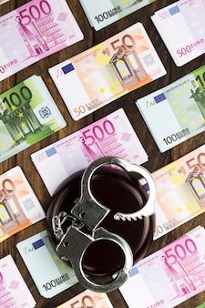 Banknoten auf holztisch mit handschellen und stand