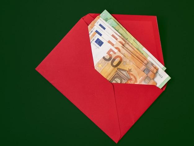 Banknoten in einem roten umschlag auf einem grünen hintergrund