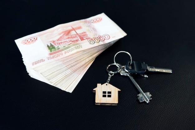 Banknoten russischer rubel und schlüssel zur wohnung auf dem schwarzen tisch. immobilienverkauf. der deal für den verkauf der wohnung. konzept.