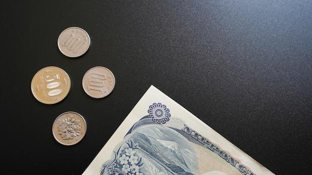Banknoten und münzen aus japanischer währung auf dunkelheit