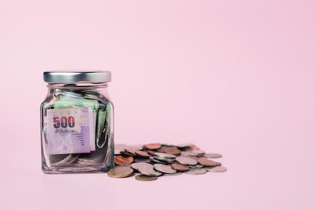 Banknoten und münzen in thailändischer währung im glas für das geschäfts-, finanz-, investitions- und sparkonzept