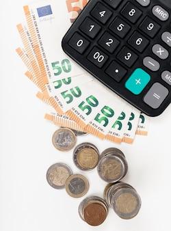 Banknoten und münzen mit taschenrechner