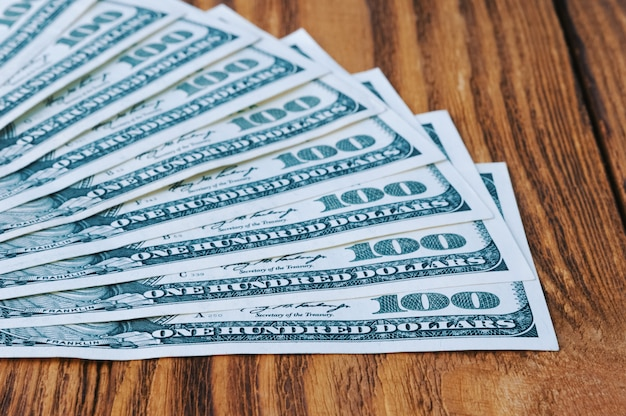 Banknoten von hundert dollar breiteten sich wie ein fächer auf den holzbrettern aus.