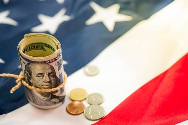 Banknotenrolle mit 100 us-dollar mit münzen auf vereinigter angegebener von amerika- oder usa-flagge