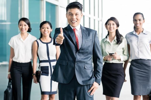 Bankpersonal vor dem büro, das sich daumen zeigt