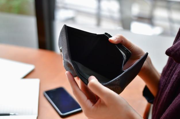 Bankrotte business-konzepte. schöne geschäftsfrau war beim öffnen einer brieftasche geschockt.