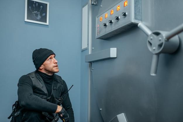 Banküberfall, männlicher räuber in schwarzer uniform, der an der tresortür sitzt. krimineller beruf, diebstahlkonzept