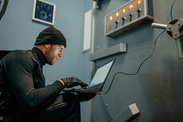 Banküberfall, männlicher räuber mit laptop, der versucht, die tresortür zu öffnen. krimineller beruf, diebstahlkonzept
