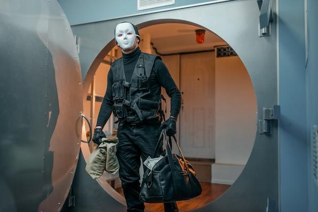 Banküberfall, räuber in schwarzer uniform und maske