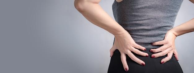 Banner der hände der frau, die auf dem unteren rücken massieren, um die schmerzen zu lindern. office-syndrom, menstruationsbeschwerden, rückenschmerzen, eingeschränkte flexibilität, nicht-chirurgische behandlungen, konzept für gesundheitssymptome bei frauen.