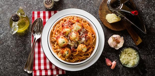 Banner der italienischen nudelspaghetti mit ricotta-käsebällchen in tomatensauce auf dem tisch mit parmesan.