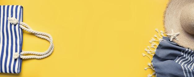 Banner der strandtasche, strohsonnenhut, strandtuch auf gelb. sommerferienhintergrund. sicht von oben.