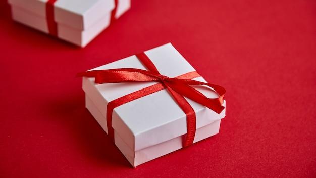 Banner der weißen geschenkboxen des luxus mit rotem band auf rotem hintergrund.
