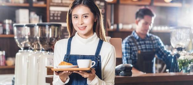 Banner des asiatischen cafébesitzers, der dem kunden im café bäckereikuchen und kaffeetasse serviert