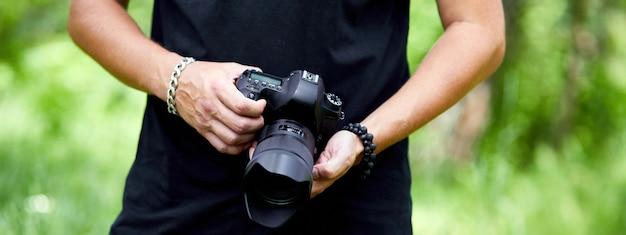 Banner des mannfotografen mit einer fotokamera in der hand im freien, weltfotografentag, kreatives hobby, kopierraum, platz für text, fotografiekonzepte professional.