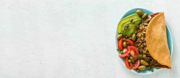 Banner des veganen frühstücks von glutenfreiem eifreiem kichererbsenomelett mit gebratenen pilzen und lauch. und ein salat aus frischen reifen tomaten, avocados, oliven und kapern.