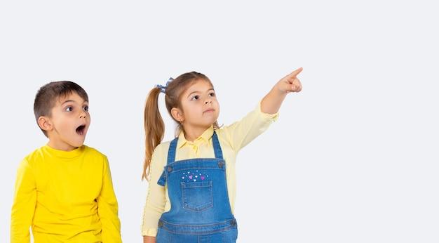 Banner. ein vorschulmädchen zeigt mit dem zeigefinger auf etwas in der ferne, der junge schaut und ist überrascht.