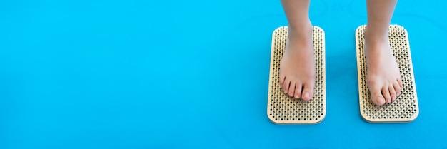 Banner. frauenfüße stehen auf einem brett mit scharfen nägeln, sadhu board. yoga-praxis. schmerz, prüfung, gesundheit. blaue yogamatte.