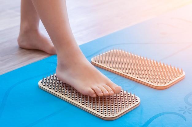 Banner. frauenfüße stehen auf einem brett mit scharfen nägeln, sadhu board. yoga-praxis. sonneneinstrahlung, strahlen. blaue yogamatte.