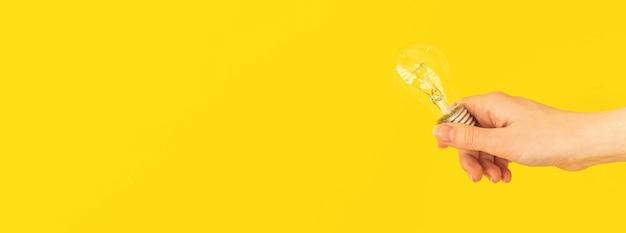 Banner-hand, die glühbirne auf gelbem hintergrund hält, neuer ideenkonzept-fotohintergrund mit kopienraum