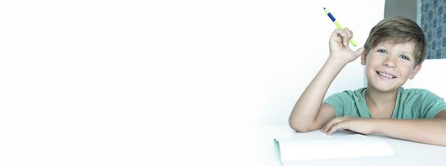 Banner. lächelnder junge mit lehrbuch macht schulhausaufgaben. zurück zur schule. glücklicher schuljunge. fernunterricht