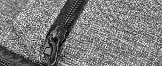 Banner mit reißverschlusstasche nahaufnahme, schwarzer textilhintergrund mit metallreißverschluss